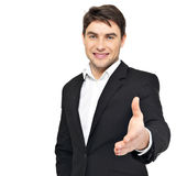 När du ler affärsmannen i svart dräkt ger handskakningen Royaltyfri Foto