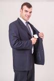 När du ler affärsmannen tar ett affärskort ut ur hans omslag royaltyfri fotografi