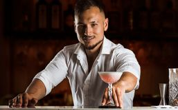 När du ler bartendern ger gästen en chic coctail i högväxta glas arkivfoto