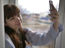 När du ler brunettflickan i en blå skjorta gör selfie vid fönstret royaltyfri foto