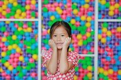När du ler den asiatiska lilla flickan håller båda händer på kinder mot färgrik bolllekplats Charmigt och positivt se uttrycker arkivbild