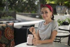 När du ler den attraktiva mörker-haired flickan med flätan har den tropiska frukosten i kafé royaltyfria bilder