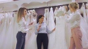 När du ler den nätta bruden väljer den vita kappan på shoppar av bröllopmode Lyckligt gifta sig begreppet stock video