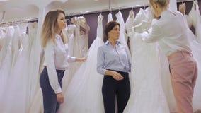 När du ler den nätta bruden väljer den vita kappan på shoppar av bröllopmode Lyckligt gifta sig begreppet arkivfilmer