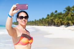 När du ler den unga kvinnan gör selfiefotoet arkivbilder