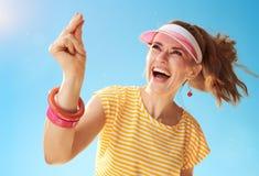 När du ler den unga kvinnan mot blå himmel fingrar att låsa fast Arkivbild