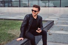 När du ler den unga mannen i solglasögon med det iklädda svarta läderomslaget för stilfullt hår rymmer smartphonen, medan sitta n royaltyfri bild