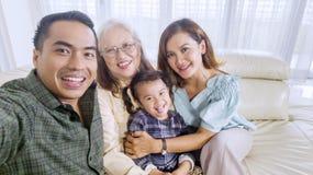 När du ler familjen tar en gruppbild hemma royaltyfri fotografi