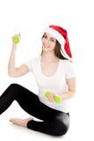 När du ler flickan i röd gräsplan för Santa Claus hatthåll färgade hanteln Arkivfoto