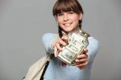 När du ler flickan isolerade grå bakgrund med kruset som var full av pengar Arkivfoton