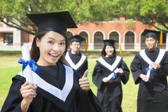 När du ler högskolakandidaten rymmer upp ett diplom och en tumme Arkivfoto