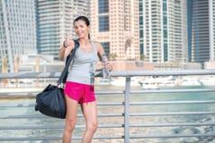 När du ler idrottsman nen visar upp tummen Idrotts- kvinna i sportswearhol Royaltyfri Bild