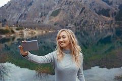 När du ler kvinnan gör selfie på bergsjön arkivbild