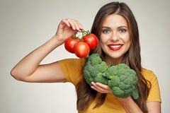 När du ler kvinnan isolerade ståenden med tomaten och broccoli Arkivfoton