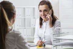 När du ler kvinnan på telefonen tar anmärkningar arkivfoton