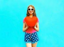 när du ler kvinnan rymmer i händer en röd ballong i formen av en hjärta royaltyfri bild
