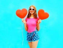 När du ler kvinnan rymmer röda ballonger för en luft i formen av en hjärta royaltyfria foton