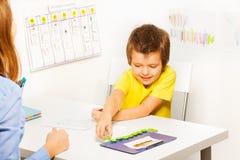 När du ler pojken sätter mynt under den framkallande leken Arkivfoton