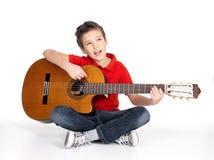 När du ler pojken spelar den akustiska gitarren Arkivfoto