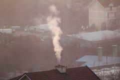 När du röker lampglas på tak av hus sänder ut rök, smog på soluppgång, föroreningar skriver in atmosfär Miljö- katastrof royaltyfri bild