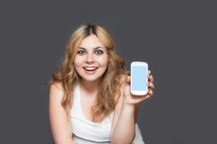 När du skrattar den tonårs- flickan visar en smart telefon Royaltyfri Foto