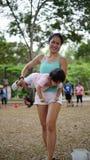 När du skrattar det bärande lilla barnet för den asiatiska kvinnan och deltagande i familj spelar utomhus- Arkivbilder