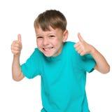När du skrattar pysen rymmer upp hans tummar royaltyfri bild