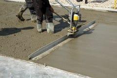 När du slätar betong med gas drev den vibrerande screedmaskinen Royaltyfri Bild