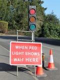 När rött ljusshower väntar här tecknet och trafikljus fotografering för bildbyråer