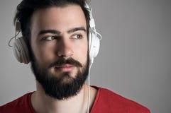 Nära ärlig siktsstående av den unga mannen med hörlurar som bort ser arkivfoton