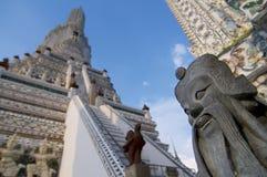 Nära övre bild av en kinesisk förmyndarestaty med Wat Arun i bakgrunden royaltyfri foto