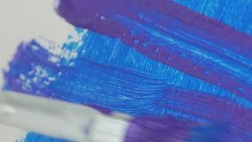 Nära övre bild med en målarfärgborste som färgar en målning med blå färg stock video