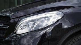 Nära övre detalj för en av de LEDDE billyktorna av en modern svart bil materiel Yttre detalj, billykta av ett prestigefullt stock video