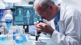 Nära övre docka som skjutas av den mogna kemisten som forskar genom att använda ett mikroskop lager videofilmer