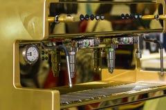 Nära övre dysa av modernt och automatiskt guld- av kaffemaskinen royaltyfri bild