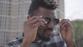 Nära övre framsida av det confidient afrikansk amerikanmananseendet mot bakgrunden av stads- byggnad som skelar i solen lager videofilmer