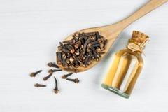 Nära övre glasflaska av kryddnejlikaolja och kryddnejlikor i träsked på den vita lantliga tabellen royaltyfria bilder