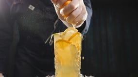 Nära övre handkock som pressar apelsinen på coctailen för ny frukt i ultrarapid fruktsaft som dreglar ut ur frukt Matlagning in stock video