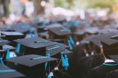 Nära övre hattgrupp av kandidater under avslutning Begreppsutbildningslyckönskan arkivfoton