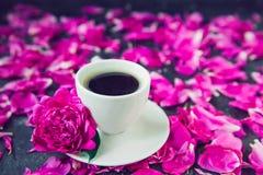 Nära övre kopp av nytt bryggat kaffe och den purpurfärgade rosa pionblomman på det vita tefatet på svart bakgrund med kronblad Go royaltyfria foton