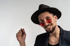Nära övre modestående av den stiliga mannen i rund solglasögon, svart dräkt och hatt arkivbild