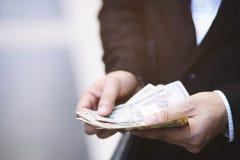 Nära övre räkning för håll för hand för anseende för affärsman pengarspridningen av kassa fotografering för bildbyråer