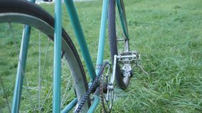 Nära övre sikt av en fast retro cykel för grönt spår på det gröna gräset arkivfilmer