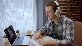 Nära övre sikt av en hapy ung gitarrist som försöker att komponera hans nya sång i ett duting kaffeavbrott för öde kafé enjoying lager videofilmer