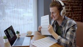 Nära övre sikt av en hapy ung gitarrist som försöker att komponera hans nya sång i ett duting kaffeavbrott för öde kafé enjoying arkivfilmer