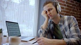 Nära övre sikt av en trött ung musiker som försöker att komponera hans nya sång i ett duting kaffeavbrott för öde kafé enjoying lager videofilmer