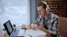 Nära övre sikt av en ung gitarrist som försöker att komponera hans nya sång i ett duting kaffeavbrott för öde kafé Tycka om arkivfilmer