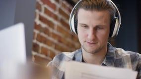 Nära övre sikt av en ung pianist eller gitarrist som försöker att komponera hans nya sång i ett duting kaffeavbrott för öde kafé stock video