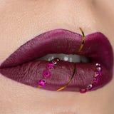 N?ra ?vre sikt av h?rliga kvinnakanter med vinous purpurf?rgad matt l?ppstift Cosmetology modemakeup Smycken p? kanter arkivbild