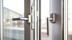 Nära övre sikt av handtag för aluminiumdörrfönster, mot ett oskarpt arkivbild